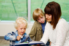 Mom reading a book to two children. Mom and children at library reading books Stock Photo