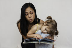 Mom reading book to 3-year-old daughter. Precious three-year-old girl sits on her mothers lap and listens to a story book. Mom is Asian and daughter is royalty free stock photography