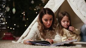 Mom is reading a daughter`s tale for the night lying with her in the tent of an established house on the background of a stock footage