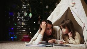 Mom is reading a daughter`s tale for the night lying with her in the tent of the house. Girl eating marmalade stock video