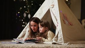Mom is reading a daughter`s tale for the night lying with her in the tent of the house. Girls are smiling stock video