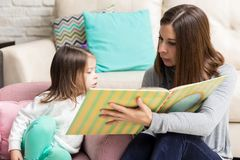 Mom Reading Fairytale To Her Daughter. Mid adult women reading story for curious daughter at home royalty free stock photography