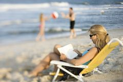 Mom Reading In Lounge Chair On Beach. Royalty Free Stock Photo