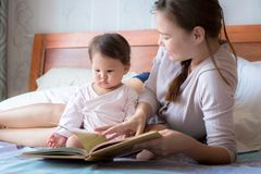 Mother reading a book to her child on the bed. Bedtime story. Learning how to read stock photo