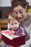 Mom reading tale to baby Stock Photos