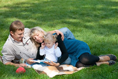 Mom reading to her family outside Stock Photos