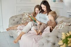 Mom reads a book to the children. A woman tells a story to a boy and a girl before going to bed. Mom daughter and son relax at hom. Mom reads a book to the