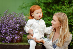 Mom and red-haired daughter holding a rabbit in the summer in th royalty free stock image