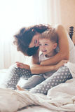 Mom relaxing with her little son. Young mother with her 2 years old little son dressed in pajamas are relaxing and playing in the bed at the weekend together stock photo