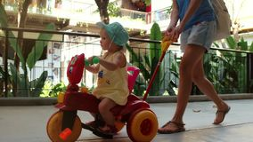 Mom riding little daughter on childrens bike while walking on summer vacation stock footage
