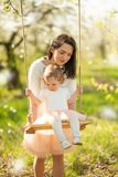 Mom rolls the baby on a swing in the flowering gardens or park, with falling flowers. Mother`s Day, March 8, spring mood.  stock photo