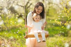 Mom rolls the baby on a swing in the flowering gardens or park, with falling flowers. Mother`s Day, March 8, spring mood. Horizontal photo royalty free stock photos