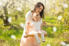 Mom rolls the baby on a swing in the flowering gardens or park, with falling flowers. Mother`s Day, March 8, spring mood. Horizontal photo stock photo