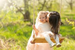 Mom rolls the baby on a swing in the flowering gardens or park. Mother`s Day, March 8, spring mood.  stock image