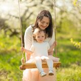 Mom rolls the baby on a swing in the flowering gardens or park. Mother`s Day, March 8, spring mood.  stock images