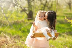 Mom rolls the baby on a swing in the flowering gardens or park. Mother`s Day, March 8, spring mood.  stock photo