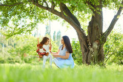 Mom rolls on a child`s swing in  park in the summer. Royalty Free Stock Photos