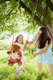 Mom rolls on a child`s swing in  park in the summer. Royalty Free Stock Images