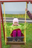 Mom rolls daughter on swing Stock Photos