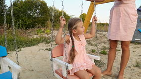 Mom rolls daughter on a swing. At the playground stock footage