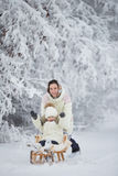Mom rolls her daughter sledging Royalty Free Stock Photos