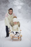 Mom rolls her daughter sledging Royalty Free Stock Photography
