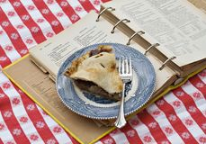 Mom's Apple Pie. A slice of apple pie on vintage plate resting on top of very old recipe book from which it was made Royalty Free Stock Images