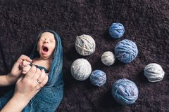 Mom`s hands hold baby wrapped in blanket amid tangles of thread. Beautiful concept of maternal love royalty free stock photography