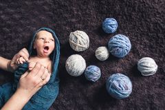 Mom`s hands hold baby wrapped in blanket amid tangles of thread. Beautiful concept of maternal love stock image