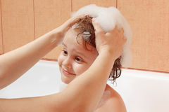 Mom's hands are washed the little blond boy's head in bathroom stock photos