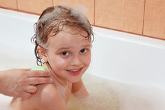 Mom's hands are washed with soap back the little blond boy Royalty Free Stock Photos