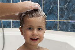 Mom`s hands washing little girly`s head in the bathroom. The sym Stock Photos