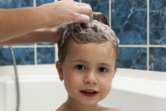 Mom`s hands washing little girly`s head in the bathroom. The sym Royalty Free Stock Images
