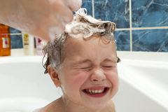 Mom`s hands washing little girly`s head in the bathroom. The sym Royalty Free Stock Photography