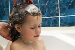 Mom`s hands washing little girly`s head in the bathroom. The sym Stock Images