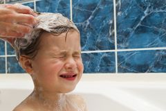 Mom`s hands washing little girly`s head in the bathroom. The sym Royalty Free Stock Photo