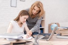Mom scolds her daughter for a bad job on the laptop. The daughter can not do the school assignment correctly. The women is angry because of this. She screams Stock Photography