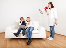 Mom screaming at kids using megaphone. Outrageous mom screaming at kids with laptop using megaphone Stock Photos
