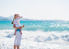 Mom on sea shore with baby pointing on copy space stock photo