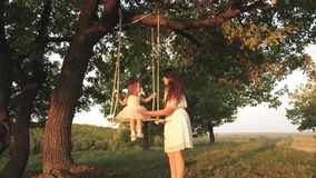 Mom shakes her daughter on swing under a tree in sun. child laughs and rejoices. mother and baby ride on a rope swing on stock video