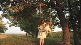 Mom shakes her daughter on swing under a tree in sun. Child laughs and rejoices. Mother and baby ride on a rope swing on stock video footage