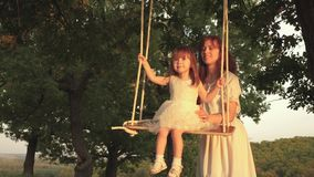 Mom shakes her daughter on swing under tree in sun. close-up. child laughs and rejoices. mother and baby ride on a rope stock video footage