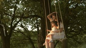 Mom shakes her daughter on swing under a tree in sun. close-up. mother and baby ride on a rope swing on an oak branch in stock footage
