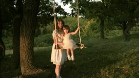 Mom shakes her daughter on swing under a tree in sun. close-up. mother and baby ride on a rope swing on an oak branch in stock video footage