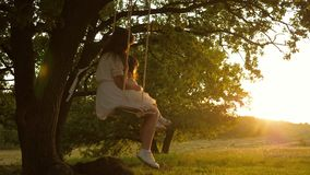Mom shakes her daughter on swing under a tree in sun. mother and baby ride on a rope swing on an oak branch in forest stock footage