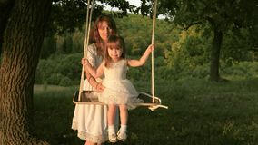 Mom shakes her daughter on swing under a tree in sun. Mother and baby ride on rope swing on an oak branch in forest stock video footage