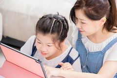 Mom show daughter how to use tablet stock images