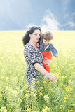 Mom showing to her son rapeseed flowers Royalty Free Stock Photography