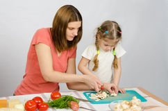 Mom shows daughter how to cut small knife mushrooms Royalty Free Stock Photography