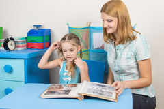 Mom shows her five-year-daughter photo album. Adult young beautiful girl shows a five-year girl in the photo album sitting at the children table at home Royalty Free Stock Photography